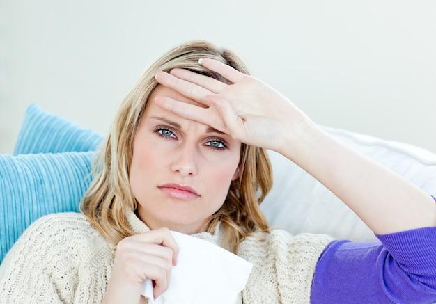 Doente mulher deitada em um sofá com tecidos e sentimento de temperatura