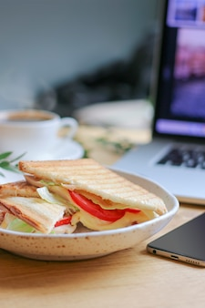 Dof raso de sanduíche vegetariano com laptop e café na parte traseira turva