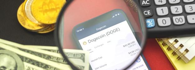 Dogecoin novo dinheiro digital virtual, criptomoeda e negociação com smartphone, banner comercial e financeiro, foto de fundo do worspace com moedas, dólares e lupa