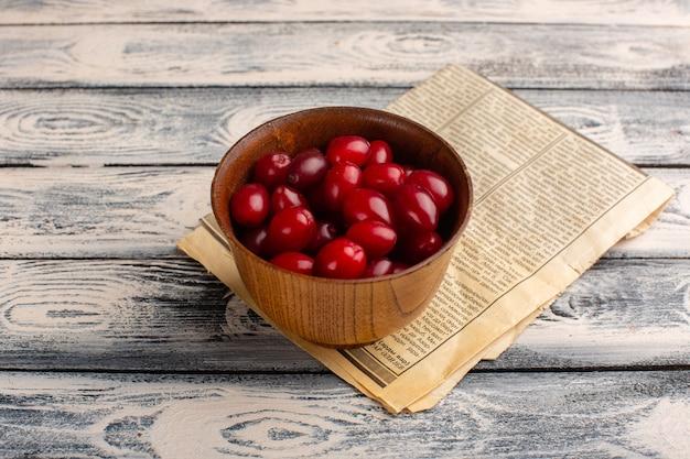 Dogwood vermelho dentro de tigela marrom em cinza