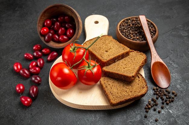 Dogwoods vermelhos frescos com pães e tomates no espaço cinza