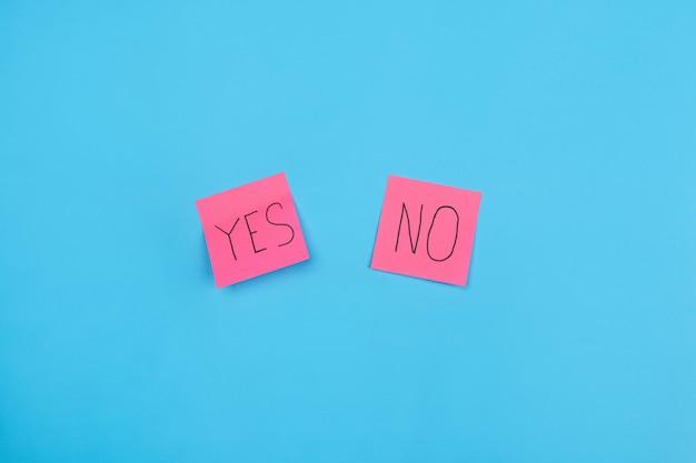 Dois adesivos rosa com a frase sim ou não em um azul. fechar-se. espaço livre para anotações.