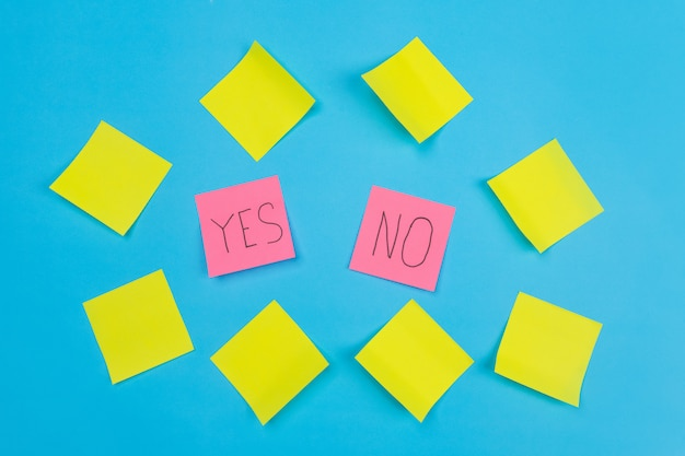Dois adesivos rosa com frases de escolha sim ou não em um azul cercado por adesivos autoadesivos amarelos. fechar-se. espaço livre para anotações.