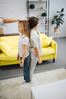 Dois adolescentes felizes ficam de costas na sala e sorriem. hol adulto mão na cabeça da menina. ele mediu o crescimento dela. menina morena parece mais alto.