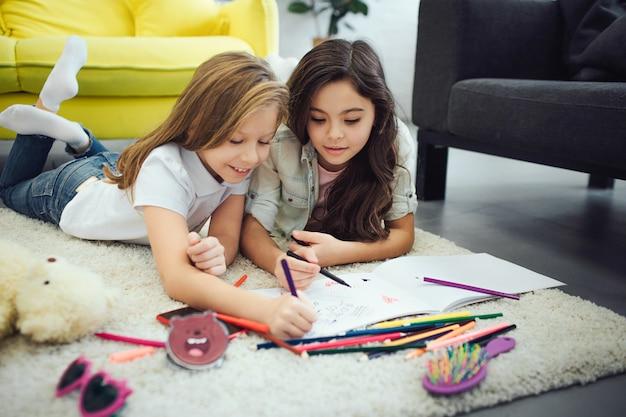 Dois adolescentes ocupados deitado tapete piso no quarto. eles desenhando.