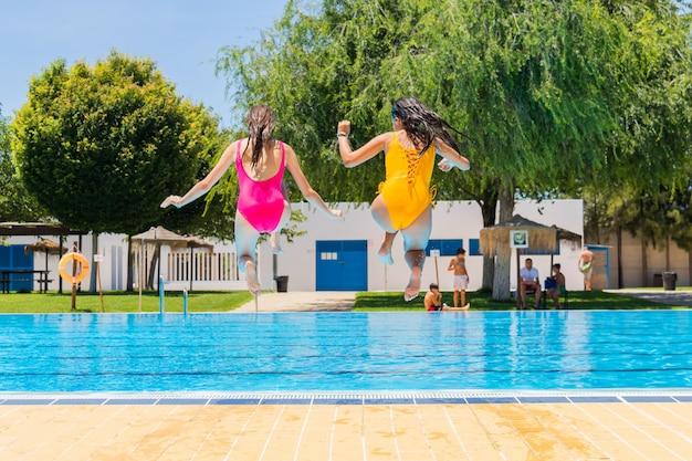 Dois adolescentes que saltam em uma piscina. duas meninas, pular, em, um, piscina