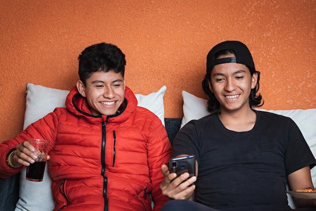 Dois adolescentes sentados em um cauch olhando para um smartphone, bebendo refrigerante e comendo pizza em uma sala de estar