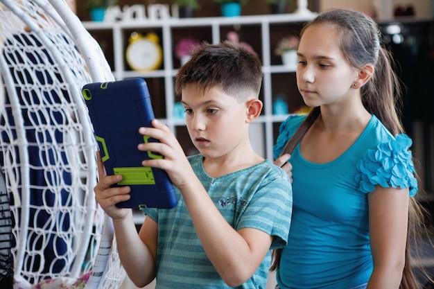 Dois adolescentes tiram fotos com um tablet