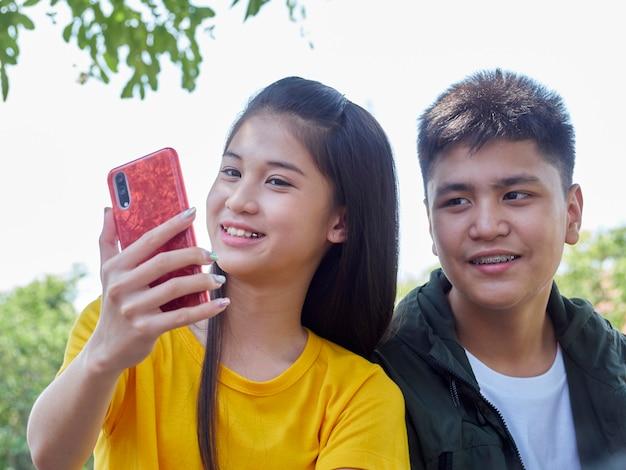 Dois adolescentes usam seus smartphones ao ar livre