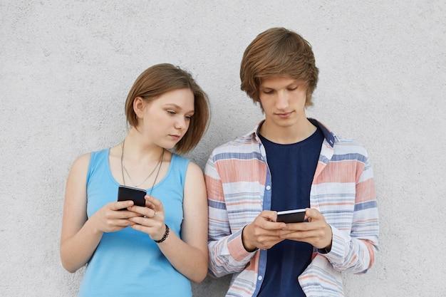 Dois adolescentes usando aparelhos modernos, jogando jogos online em pé contra a parede de concreto cinza