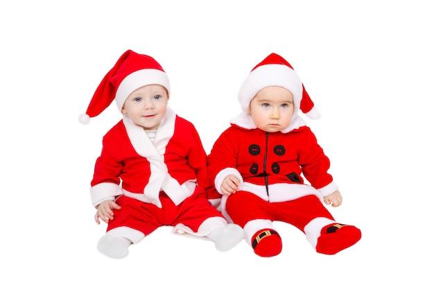 Dois adoráveis bebês estão sentados com o terno de papai noel e o chapéu.