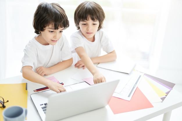 Dois adoráveis meninos latinos, irmãos olhando focados enquanto estão sentados juntos à mesa e usando o laptop. crianças tendo aula online em casa. educação a distância durante o conceito de bloqueio