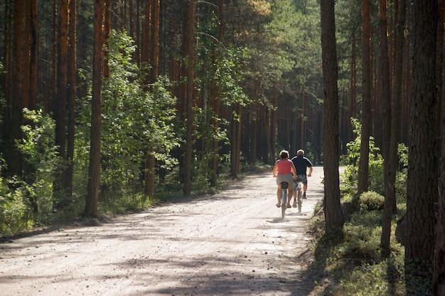 Dois adultos andam de bicicleta em uma estrada de terra na floresta, vista de trás