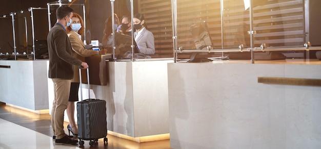 Dois adultos com máscaras médicas em pé com suas bagagens em frente a um vidro afastado da recepção