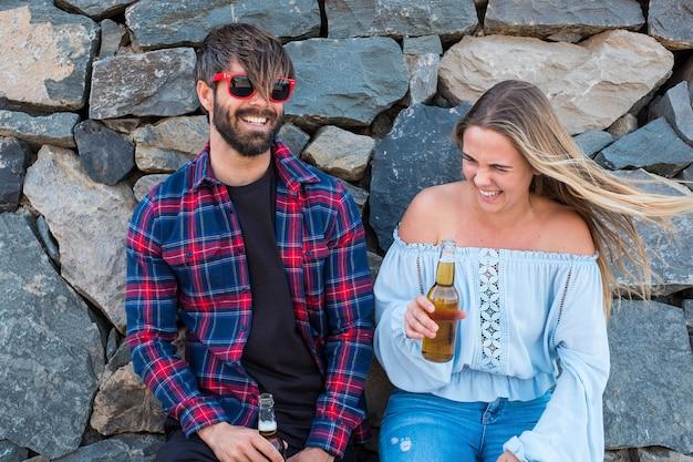 Dois adultos se divertindo, conversando e rindo juntos, bebendo uma cerveja - homem com óculos de sol vermelhos desfrutando - conceito e encontro do primeiro encontro