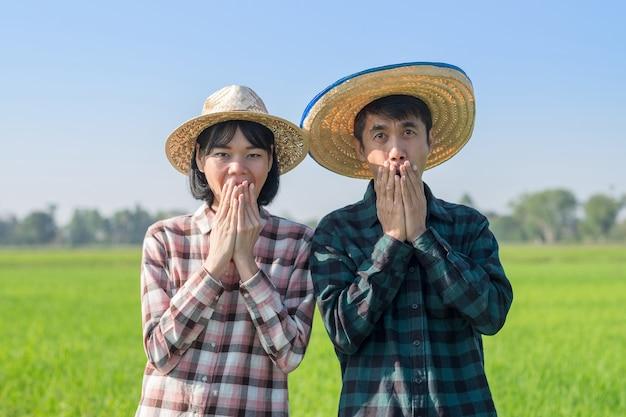 Dois agricultores asiáticos em pé com cara de surpresa wow em uma fazenda de arroz verde. conceito de alguns fazendeiros.