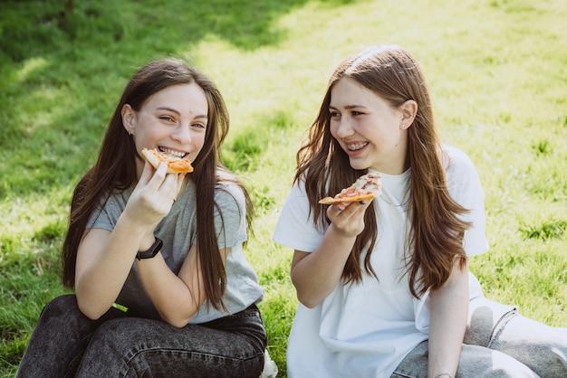 Dois alegres amigos adolescentes no parque comendo pizza. as mulheres comem fast food. não é uma dieta saudável. foco seletivo suave.