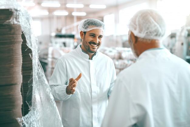 Dois alegres trabalhadores caucasianos da fábrica de alimentos em uniformes brancos e com redes para o cabelo em pé e falando sobre a produção de alimentos.