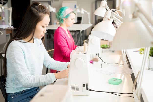 Dois alfaiates femininos em máquinas de costura