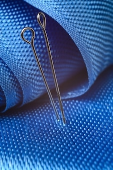 Dois alfinetes de costura em um fundo de tecido azul. fechar-se.