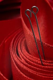 Dois alfinetes de costura no fundo de uma fita vermelha. fechar-se.