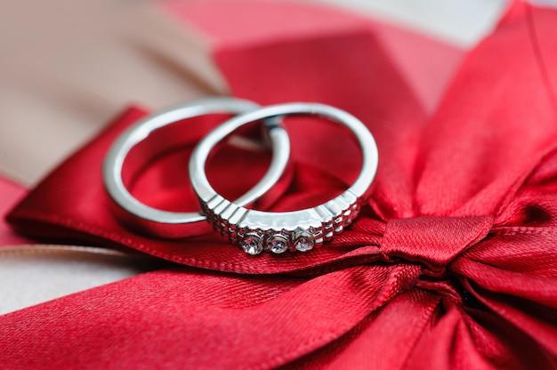Dois, alianças casamento, ligado, fita vermelha