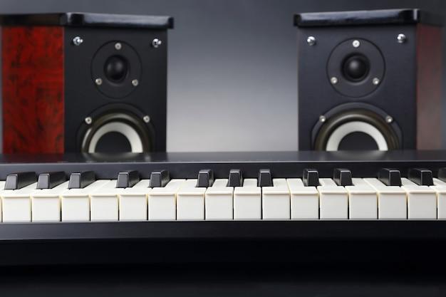 Dois alto-falantes de áudio estéreo e close up das teclas do piano no escuro