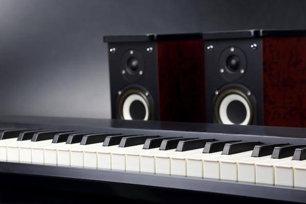 Dois alto-falantes de áudio estéreo e close up de teclas de piano em fundo escuro