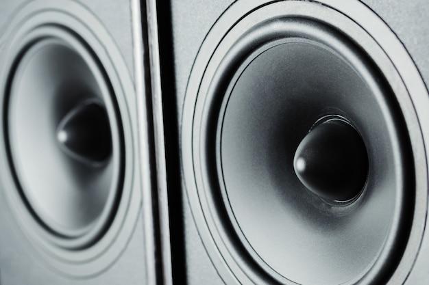 Dois alto-falantes de som de áudio em fundo escuro, close-up