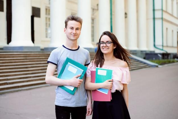 Dois alunos alegres, segurando cadernos e pastas.