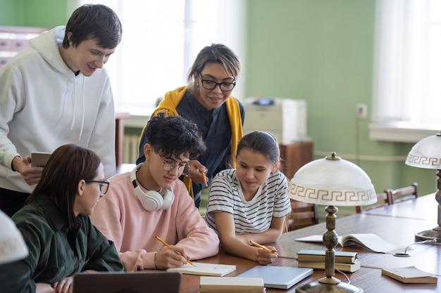 Dois alunos apontando para anotações de um adolescente em seu bloco de notas enquanto escolhem o nome do projeto em grupo na biblioteca da faculdade