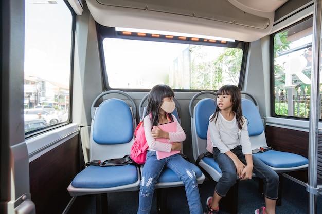 Dois alunos asiáticos do ensino fundamental indo para a escola de ônibus e transporte público