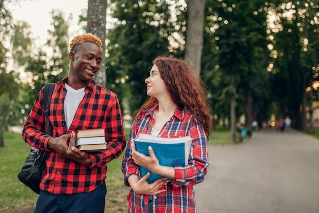 Dois alunos caminham na calçada de um parque de verão. adolescentes brancos do sexo masculino e feminino ao ar livre