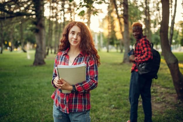 Dois alunos caminhando no gramado de um parque de verão