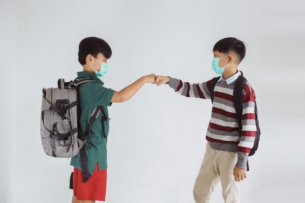 Dois alunos com máscara médica fazendo colisão com o punho impedindo o vírus corona