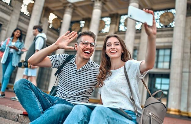 Dois alunos com mochilas e um laptop sentam-se nos degraus perto do campus e tiram uma selfie em um smartphone.