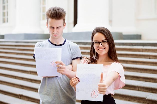 Dois alunos com resultados dos testes. aluna feliz recebeu uma nota a excelente, mas seu amigo falhou no teste e recebeu nota baixa por seu trabalho