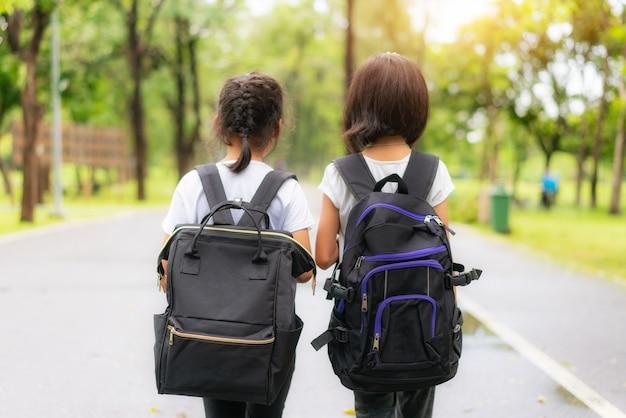 Dois alunos da escola primária caminhando vão para a escola.