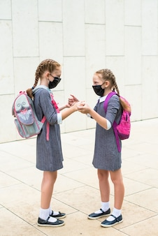 Dois alunos do ensino fundamental, com máscaras médicas