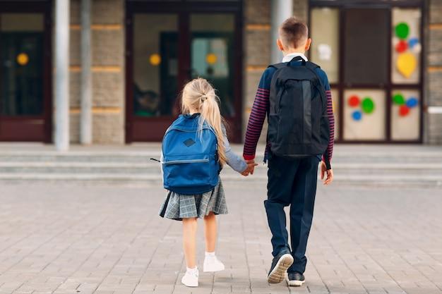 Dois alunos do ensino fundamental, irmão e irmã, voltando para a escola.