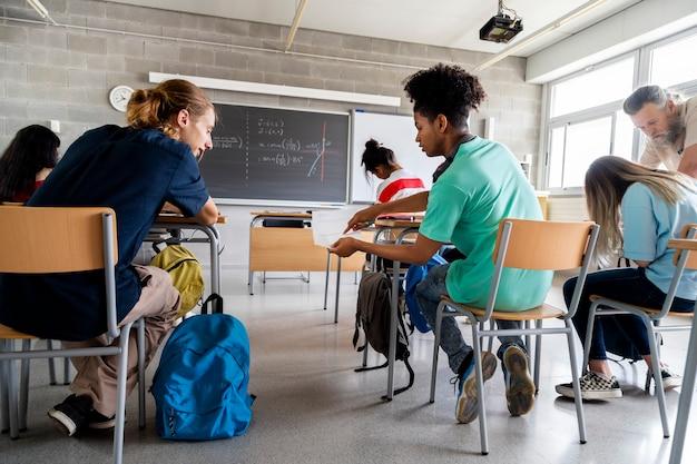 Dois alunos do sexo masculino do ensino médio trabalham juntos e o professor ajuda o aluno com o dever de casa.
