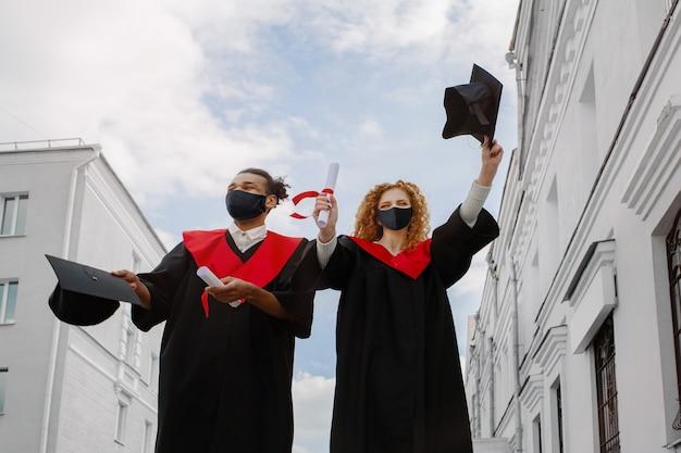 Dois alunos felizes de pós-graduação em vestidos e máscaras estão felizes. eles seguram um almofariz preto com borla vermelha e diplomas na mão após a cerimônia