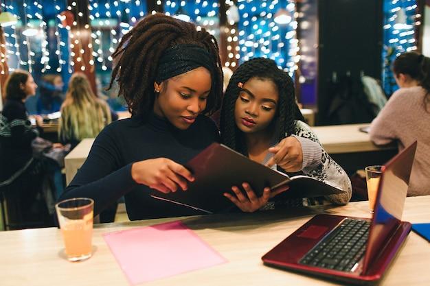 Dois alunos olham diário aberto