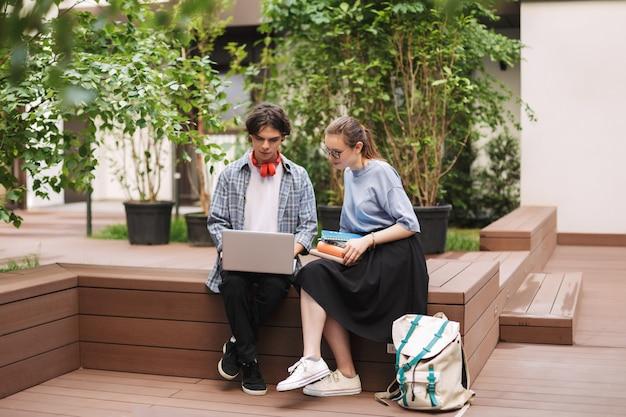 Dois alunos sentados no banco com livros e trabalhando em um laptop no pátio da universidade