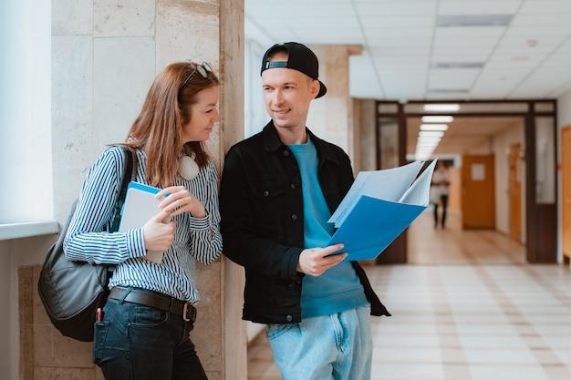 Dois alunos, um garoto e uma garota, estão caminhando pelo corredor da universidade e discutindo material educacional