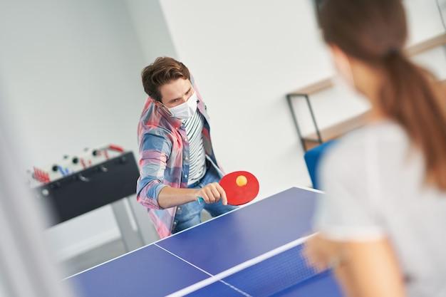 Dois alunos usando máscaras enquanto jogam tênis de mesa no campus
