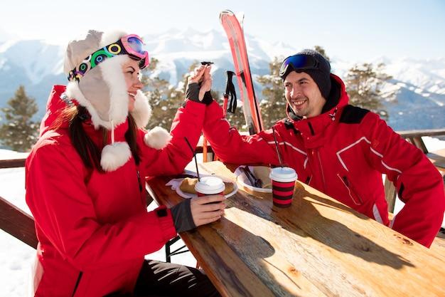 Dois amantes e amigos desfrutando de bebida no bar na estância de esqui.