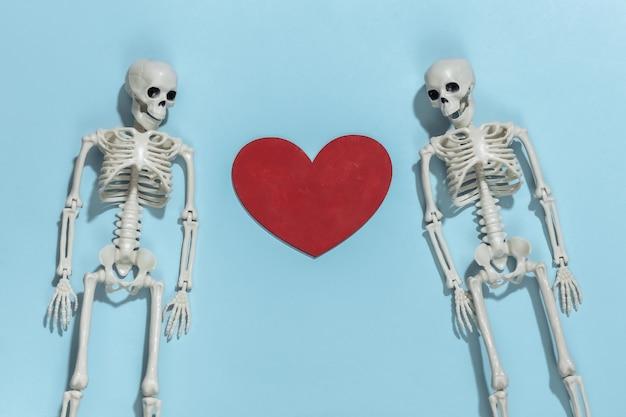 Dois amantes esqueletos e coração decorativo vermelho sobre um fundo azul brilhante. dia dos namorados ou tema de halloween.