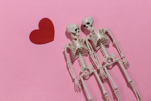Dois amantes esqueletos e coração decorativo vermelho sobre um fundo rosa brilhante. dia dos namorados ou tema de halloween.
