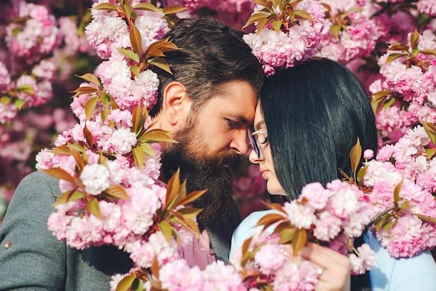 Dois amantes estão abraçando e beijando ao ar livre. feliz dia dos namorados. jovem casal romântico entre flores de sakura rosa. ame. dia de primavera.